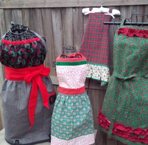 Aprons for everyone on your gift list! From left to right; Josephine in black check with wreath print; Anneliese child's apron in candy canes and velvet trim, Lily in tartan plaid with a holly print box pleat, and Natalie in a dark green holly with maroon ruffles. All are available now in our catalog!