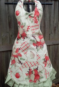 Susan apron in a soft cream and green fruit motif. Removable bow for bodice or pocket.